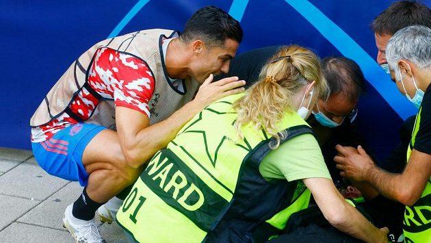 Cristiano Ronaldo z Manchesteru United u zasažené pořadatelky ležící na zemi.