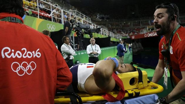 Zraněného francouzského gymnastu Samira Aita Saida odnášejí zdravotníci na nosítkách.