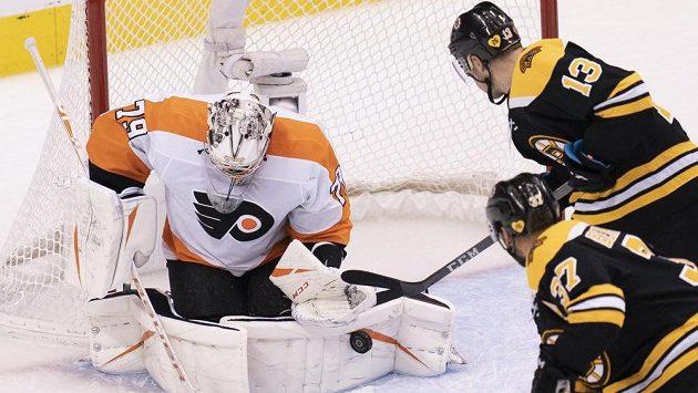 Brankář Philadelphie Flyers Carter Hart (79) likviduje šanci bostonského centra Charlieho Coyla (13), v akci je elitní útočník Bruins Patrice Bergeron (37).