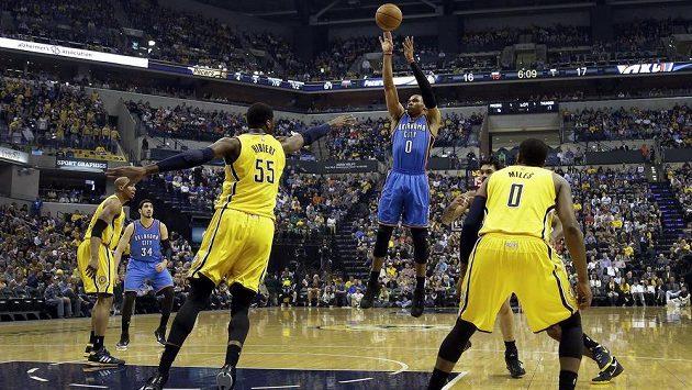 Basketbalista Oklahomy Russell Westbrook (vzadu v modrém) střílí na koš Indiany.