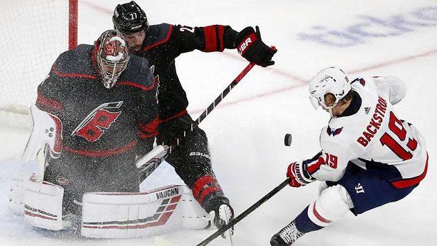 Hokejista Caroliny Justin Faulk (27) pomáhá brankáři Petru Mrázkovi při blokování střely Nicklas Backströma z Washingtonu.