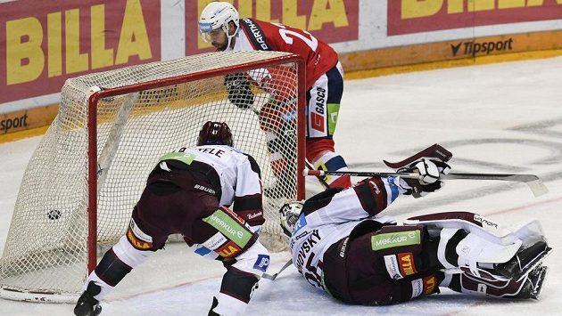 Michal Vondrka z Pardubic střílí první gól. Vpředu zleva Jan Buchtele a brankář Matěj Machovský, oba ze Sparty.