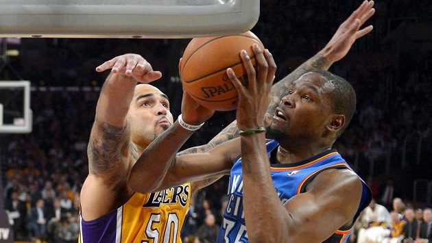 Kevin Durant (vpravo) z Oklahomy se snaží ve výskoku prosadit přes bránícího Roberta Sacreho z Los Angeles Lakers.