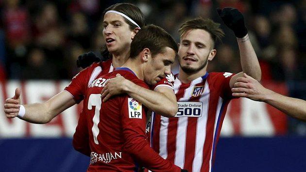 Antoine Griezmann (7) a jeho spoluhráči Filipe Luís se Saulem Niguezem slaví třetí gól Atlétika Madrid proti San Sebastianu.