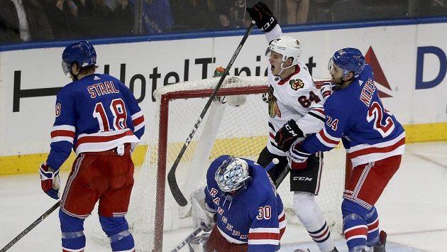 Český útočník David Kämpf se mezi hráči New York Rangers raduje z vítězného gólu spoluhráče Patricka Sharpa z Chicaga.