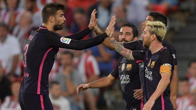 Fotbalisté Barcelony Gerard Piqué, Luis Suárez a Lionel Messi se radují z výhry v Bilbau.