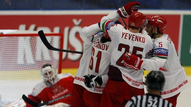 Bělorouští hokejisté se radují z gólu proti Dánsku v utkání na MS v Ostravě. V pozadí jejich oslavu sleduje brankář Patrick Galbraith (vlevo).