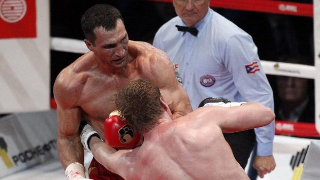 Alexandr Povětkin inkasuje tvrdý úder od Vladimira Klička v mistrovském duelu organizací WBO, IBF a IBO.