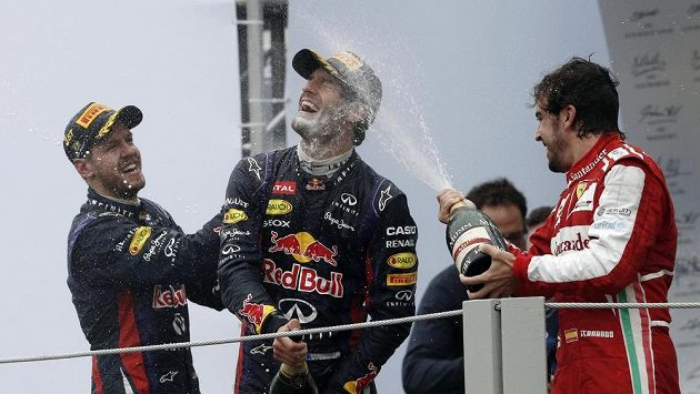 Tumáš na rozloučenou! Sebastian Vettel (vlevo) a Fernando Alonso (vpravo) kropí šampaňským Marka Webbera, který v Brazílii uzavřel svou kariéru ve formuli 1.