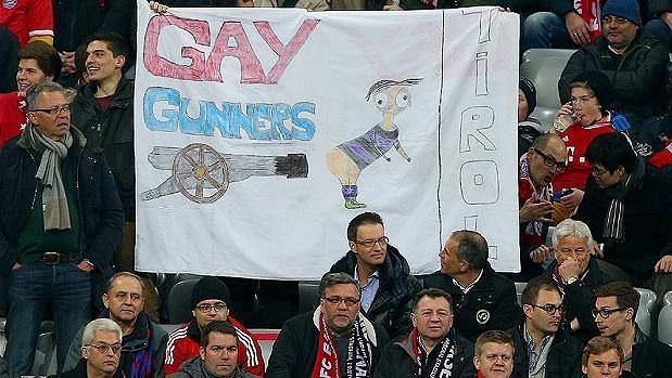 """Transparentem """"Homosexuální Kanonýři"""" urážela část fanoušků Bayernu v březnovém utkání Ligy mistrů fotbalisty Arsenalu. Posloužila jim k tomu i karikatura Mesuta Özila."""