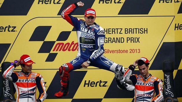 Jorge Lorenzo (uprostřed) se raduje z triumfu ve Velké ceně Velké Británie v třídě MotoGP.