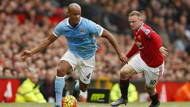 Na Vincenta Kompanyho z Manchesteru City (vlevo) doráží útočník Manchesteru United Wayne Rooney.