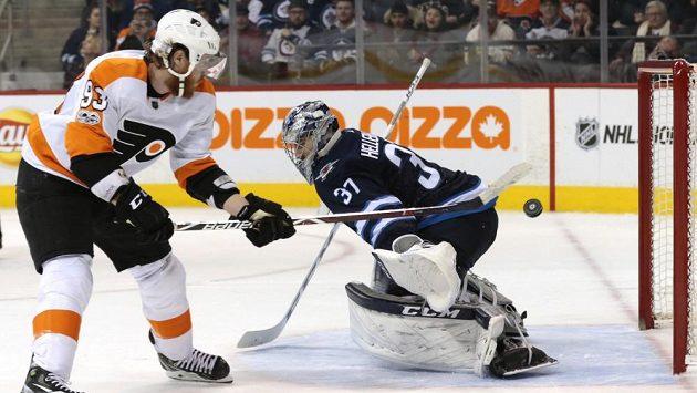 Český hokejista Jakub Voráček překonává Connora Hellebuycka v penaltovém rozstřelu v utkání na ledě Winnipegu.