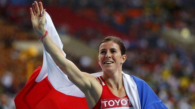 Zuzana Hejnová s českou vlajkou zdraví fanoušky po triumfu ve finále na 400 m překážek na MS v Moskvě.