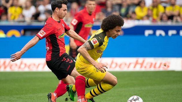 Fotbalista Dortmundu Axel Witsel padá po souboji o míč s Nicolasem Hoflerem z Freiburgu v utkání nejvyšší německé soutěže.