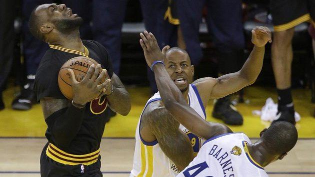 Hvězda Clevelandu LeBron James (vlevo) se snaží prosadit přes dvojici bránících hráčů Golden State Harrisona Barnese a Andrého Iguodalu.