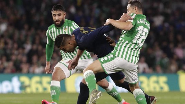 Fotbalista Realu Madrid Casemiro bojuje o míč s hráči Betisu v utkání španělské ligy.