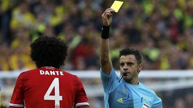 Ital Nicola Rizzoli (vpravo) dává žlutou kartu ve finále Ligy mistrů obránci Bayernu Mnichov Dantemu.