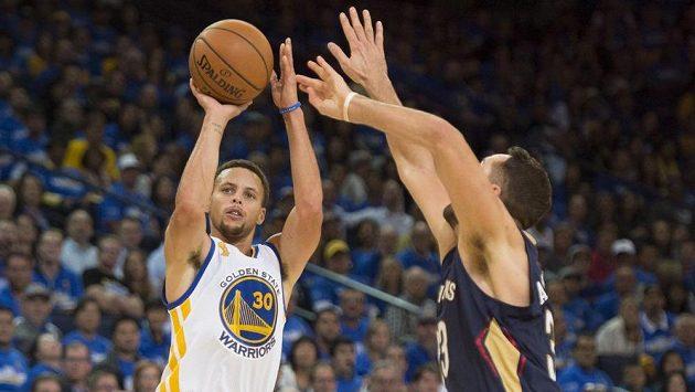 Stephen Curry z Golden State (vlevo) střílí přes obránce New Orleans Ryana Andersona.