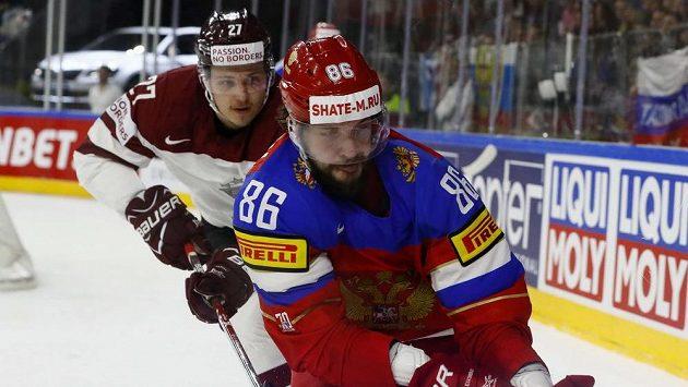Ruský hokejista Nikita Kučerov pronásledovaný Lotyšem Oskarsem Cibulkisem.