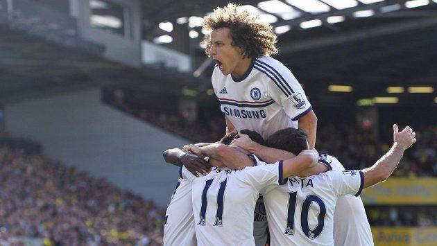 Obránce Chelsea David Luiz (nahoře) slaví se spoluhráči gól Oscara proti Norwichi.