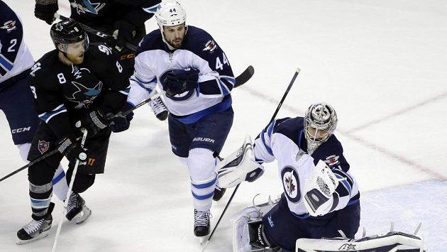 Brankář Winnipegu Ondřej Pavelec zasahuje v utkání proti San Jose. Přihlíží obránce Jets Zach Bogosian (uprostřed). Vlevo sleduje celou situaci útočník Sharks Joe Pavelski.