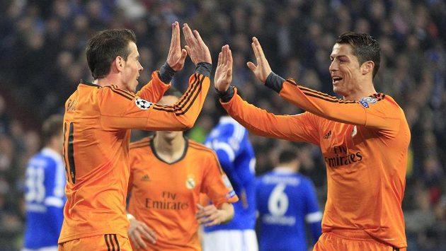 Cristiano Ronaldo (vpravo) gratuluje střelci Garethovi Baleovi k brance na hřišti Schalke.