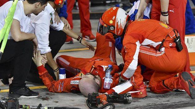 Zraněný mechanik Ferrari leží na zemi poté, co mu Kimi Räikkönen přejel nohu.