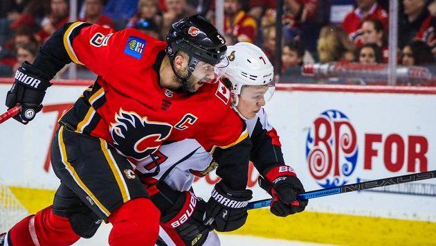 Levé křídlo Ottawy Senators Brady Tkachuk svádí souboj s obráncem Calgary Flames Markem Giordanem.