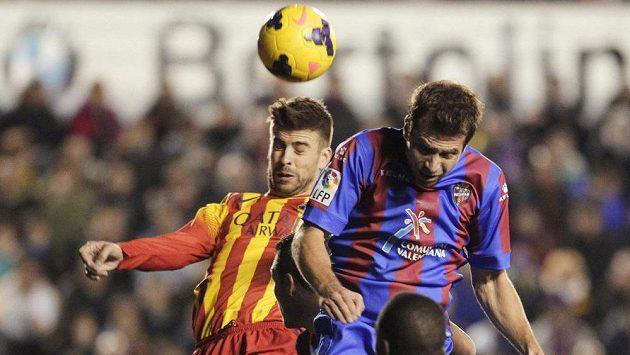 Vlevo Gerard Piqué z Barcelony hlavičkuje míč před Andreasem Ivanschitzem z Levante.
