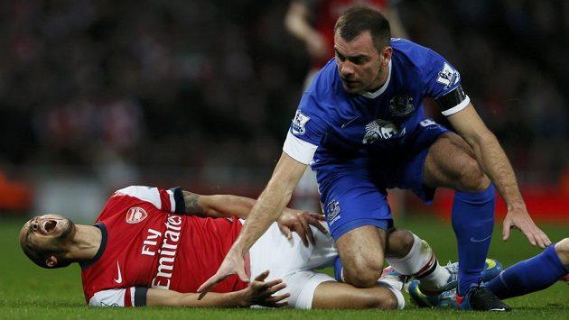 Theo Walcott z Arsenalu se svíjí na trávníku po střetu s Darronem Gibsonem z Evertonu.