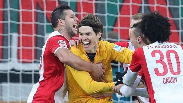 Brankář Marwin Hitz v objetí spoluhráčů z Augsburgu poté, co gólem v nastavení zajistil domácímu týmu remízu v utkání s Leverkusenem.