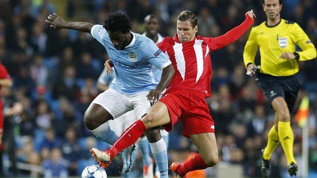 Wilfried Bony (vlevo) z Manchesteru City v tvrdém souboji s Grzegorzem Krychowiakem ze Sevilly.