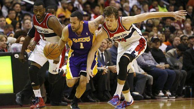 Basketbalista Los Angeles Lakers Jordan Farmar (uprostřed) se prodírá mezi dvojící bránících hráčů Washingtonu Wizards Johnem Wallem a Janem Veselým (vpravo).