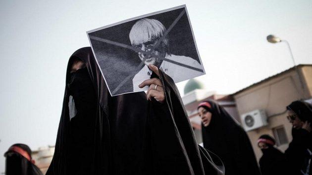 Protestující bahrajnská žena s přeškrtnutým portrétem hlavního promotéra formule 1 Bernieho Ecclestona.