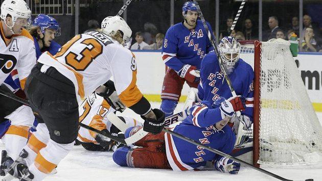 Útočník Philadelphie Flyers Jakub Voráček (zády) doráží puk před brankou New Yorku Rangers.