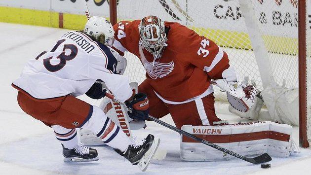 Brankář Detroitu Red Wings Petr Mrázek zastavuje pokus Cama Atkinsona (13) z Columbusu.