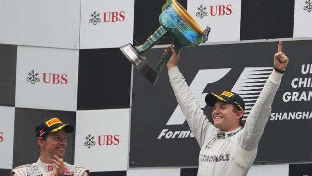 Nico Rosberg se v Číně raduje ze svého premiérového vítězství ve formuli 1. Vpravo druhý Jenson Button.