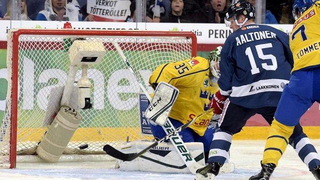 Finský útočník Miro Aaltonen střílí gól švédskému brankáři Niklasu Svedbergovi.