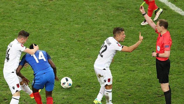 Rozhodčí William Collum uděluje žlutou kartu Amiru Abrashimu z Albánie v duelu proti Francii.
