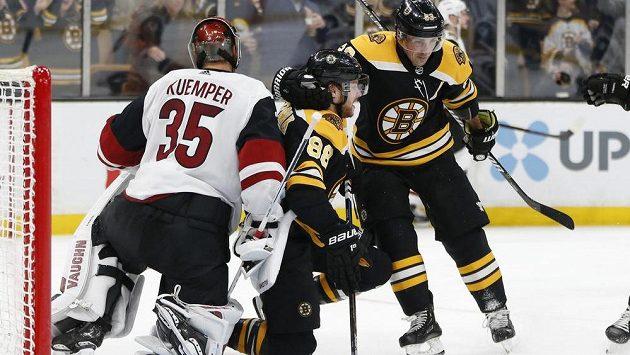 Český útočník David Pastrňák (88) skóroval v utkání NHL proti Arizoně. K přesné trefě mu gratuluje spoluhráč Brad Marchand (63). Vše sleduje překonaný gólman týmu Coyotes Darcy Kuemper (35).