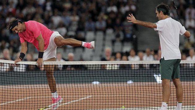 Rafael Nadal (vlevo) přeskakuje síť a Nadal na něj pobaveně zírá.