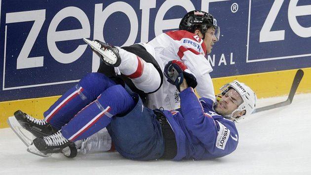 Francouzský hokejista Yorick Treille (níže) v souboji s Rakušanem Mariem Altmannem během utkání MS v Praze.