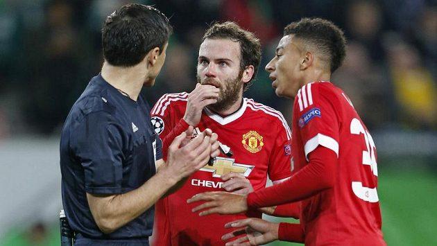 Fotbalisté Manchesteru United Jesse Lingard (vpravo) a Juan Mata diskutují s rozhodčím. Ptají se ho snad na cestu na Letnou...?