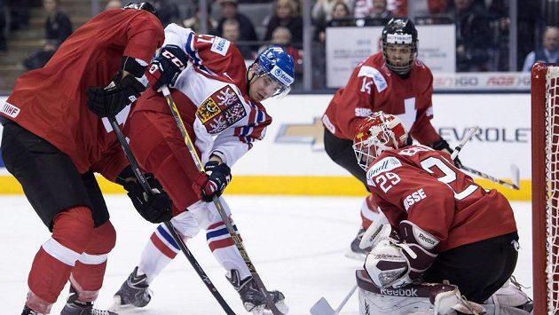 Český obránce Dominik Mašín (druhý zleva) se snaží zasunout puk za záda švýcarského brankáře Gauthiera Desclouxe.