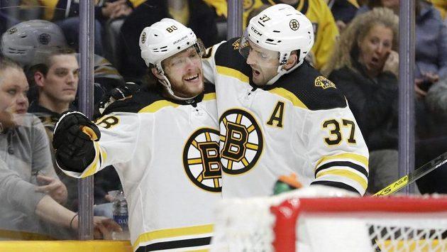 Hokejový útočník David Pastrňák slaví další gól. Raduje se z něj se spoluhráčem z Bostonu Patricem Bergeronem (37) v utkání NHL na ledě Predators.