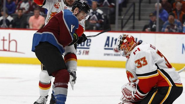 Hokejista Colorada Avalanche Matt Calvert před brankářem Calgary Davidem Rittichem.