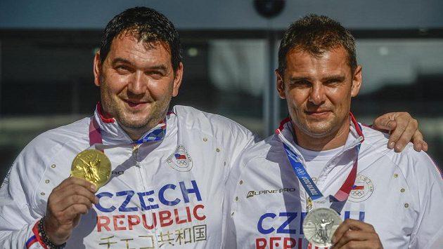 Sportovní střelci Jiří Lipták (vlevo) a David Kostelecký po příletu na Letiště Václava Havla v Praze ukazují své medaile z olympiády v Tokiu.