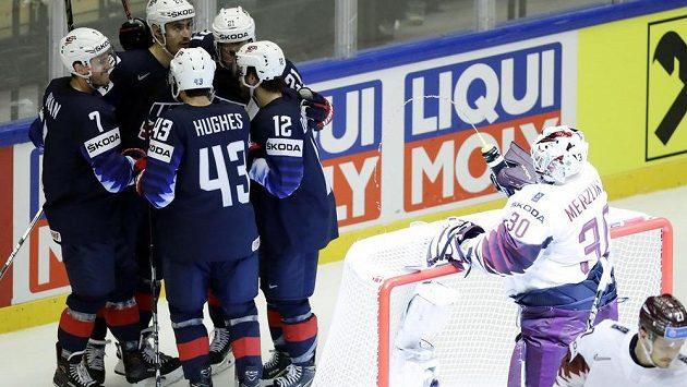 Lotyšský brankář Elvis Merzlikins stříká vodu z lahve směrem ke slavícím Američanům po gólu Chris Kreidera.