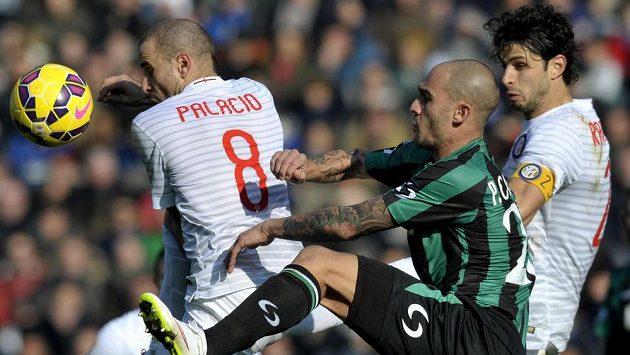 Obránce Sassuola Paolo Cannavaro (v zeleném dresu) v souboji s útočníkem Interu Milán Rodrigem Palaciem v utkání 21. kola italské ligy. Vpravo je stoper Andrea Ranocchia.